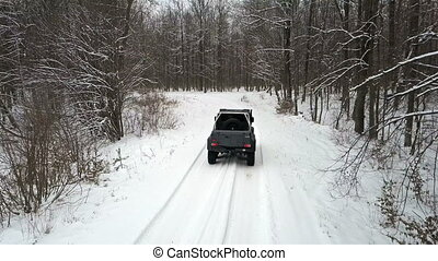 SUV 6x6 rides by winter road in snow-covered forest, back view
