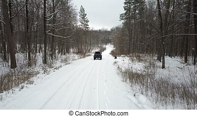 SUV 6x6 rides by winter road in snow-covered forest