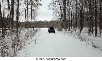 SUV 6x6 rides on a snow-covered road in a winter forest, rear view