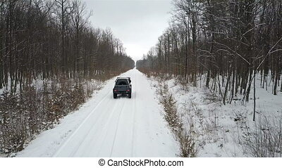 SUV 6x6 rides on a winter road in a snowy forest, back view