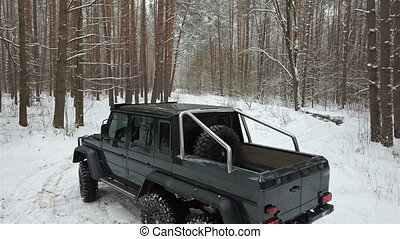 SUV 6x6 standing on a snow-covered road in winter forest, aerial view. Off-road