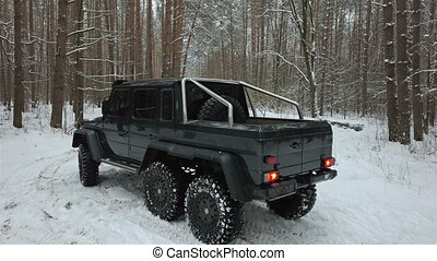 SUV 6x6 standing on a snow-covered road in winter forest, aerial view