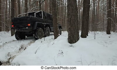 SUV 6x6 standing on a snow-covered road in winter forest, back view