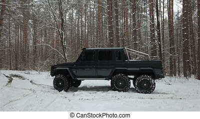 SUV 6x6 standing on a snow-covered road in winter forest, side view. Off-road