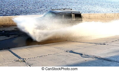 SUV drives through a puddle at speed