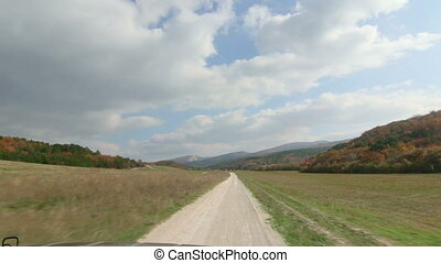 SUV driving on dirt road between hills in the Crimean mountains