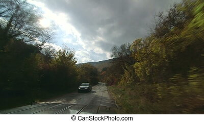 SUV driving on mountain road through forest in autumn