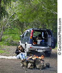 SUV Fun - A woman next to a SUV and burning bonfire...