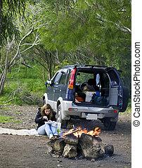 SUV Fun - A woman next to a SUV and burning bonfire...