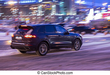 SUV moves at night along the city street