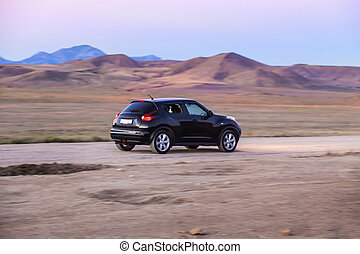 SUV is driving on a road in a mountainous area.