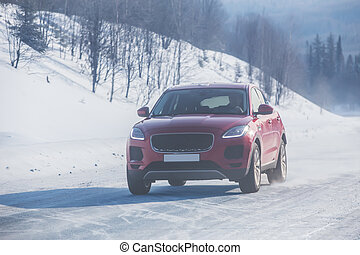 SUV moves in the winter on a country road