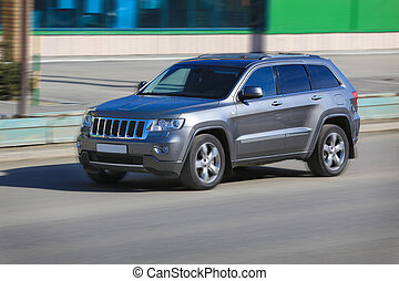 SUV moves on the city street - modern SUV moves on the city...