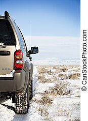 SUV on the road to nowhere - SUV on a remote snowy road,...
