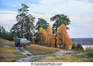 SUV on the shore of a beautiful lake in autumn