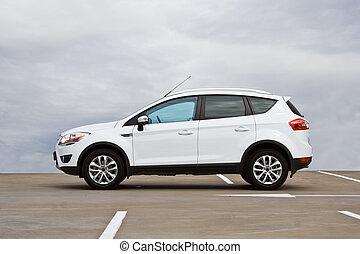Side view of a compact SUV. Cloudy sky.