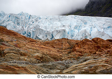 Glacier ice and rust colored mountain