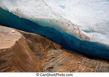 Glacier ice and rust colored rocks
