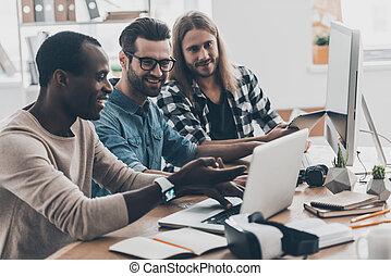 sviluppo, nuovo, project., gruppo, di, successesful, giovani persone, lavorare insieme, e, sorridente, mentre, seduta, a, il, scrivania, in, creativo, ufficio