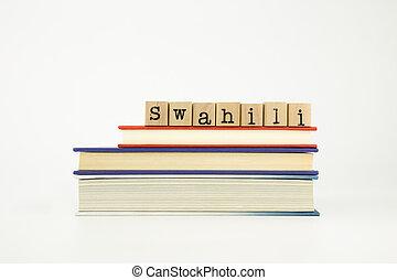 swahili language word on wood stamps and books - swahili...
