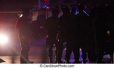 Silhouette of SWAT officers with riffles standing by police truck