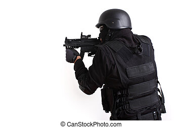 SWAT police officer aiming assault gun.