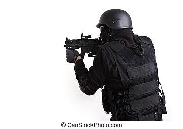 SWAT police officer aiming assault gun.