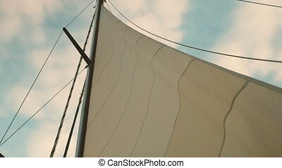 Swaying sails of yacht against backdrop cloudy sky on summer day.