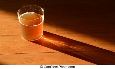 Swaying tea in glass on a wood floor which exposed to the...
