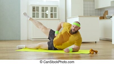 Sweaty fat man in yellow wet sportswear is doing legs lifting exercises lying on mat at home, side view. Sport, workout, training, willpower concept. Joke, mem, fitness, humor, fun behavior.