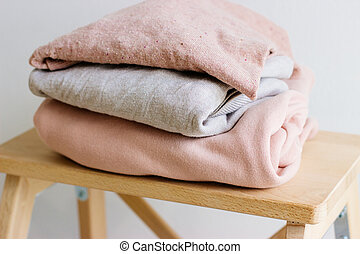 Sweaters lie on a wooden shelf.