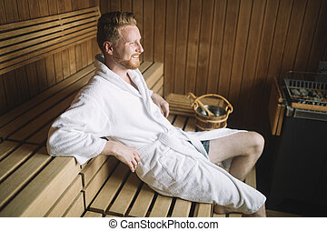 Sweating attractive man laying in a sauna