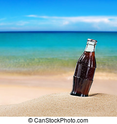sweating bottle of cola on the sand - sweating bottle of...
