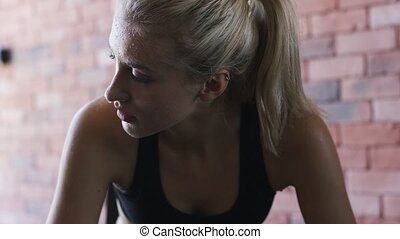 Sweaty sportswoman looking away - Tired young female with...