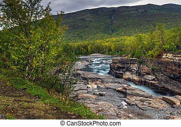 Cloudy fall autumn view of Abisko National Park, Kiruna Municipality, Lapland, Norrbotten County, Sweden, with Abiskojokk river and Nuolja mountain, near border of Finland, Sweden and Norway