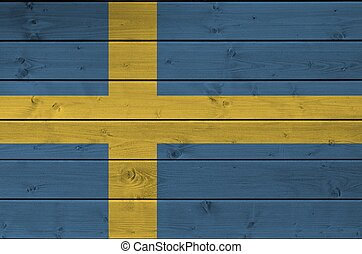 Sweden flag depicted in bright paint colors on old wooden wall. Textured banner on rough background