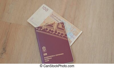 Picture of a Swidish Passport (with the words European Union Sweden Passport in Swedish) with a 100 Moroccan Dirhams Bill Partially Inside
