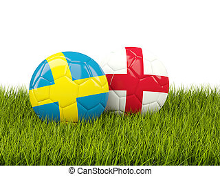 Sweden vs England. Soccer concept. Footballs with flags on green grass
