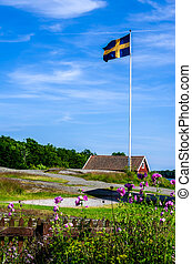 Swedish archipelago with a red house on the rocks and a flagpole with the flag.