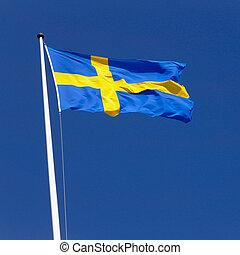 Swedish flag flies sunlit in the fresh wind on a flagpole...