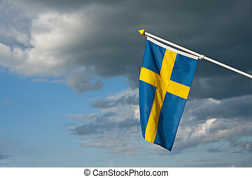 Swedish flag on typical Swedish summer sky