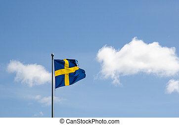 Swedish flag waving at a summer sky