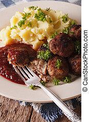 Swedish food: meatballs kottbullar, lingonberry sauce and mashed potatoes macro. Vertical
