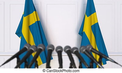 Swedish official press conference. Flags of Sweden and...