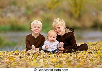 Swee Happy Children Sitting in Fallen Leaves