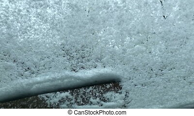 Sweep snow from the car windshield in slow motion