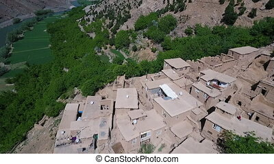 Sweeping birds eye view of desert mountain village. - Homes...