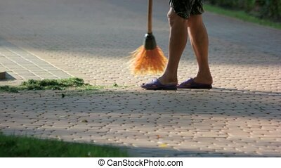 Sweeping cut grass from cobblestone pavement. Public janitor...