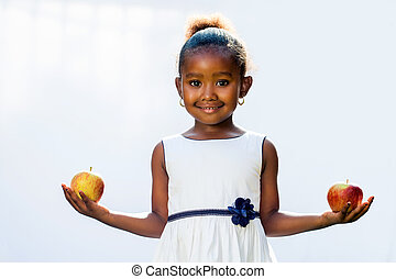 Sweet african girl holding apple in each hand.