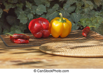 Sweet and bitter pepper against a background of green ivy